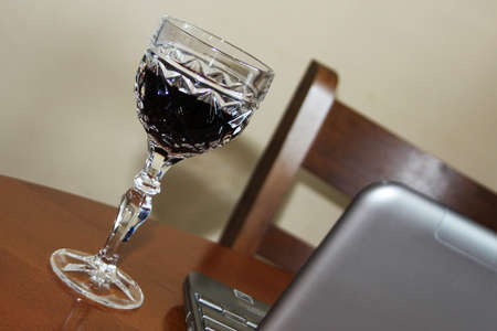 expectation: Empty seat, laptop and glass of red wine in expectation