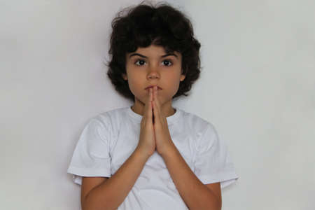 Studio portrait of a boy with hands together for supplication Stock Photo - 17193702