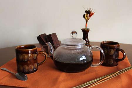Naturaleza muerta con cafetera de caf�, dos tazas de cer�mica y plato con dulces en tela de color naranja Foto de archivo - 17456743