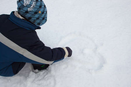 A child is drawing heart in the snow Stock Photo - 17418479
