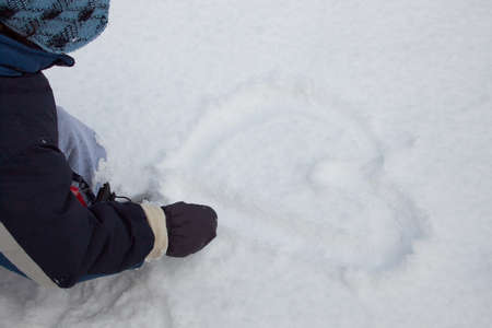A child is drawing heart in the snow Stock Photo - 17418478