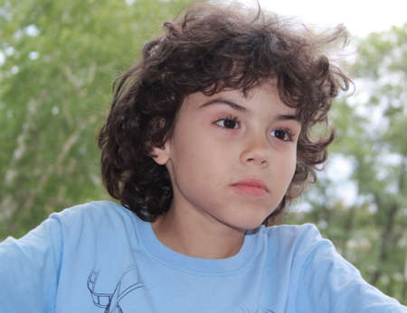 Cute little boy with curly hair is posing in front of camera photo