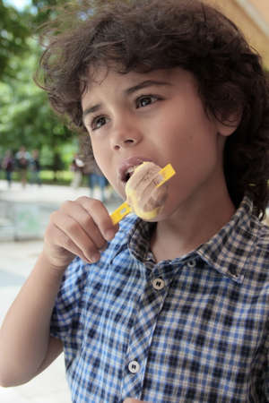 Curly boy is eating an ice cream photo