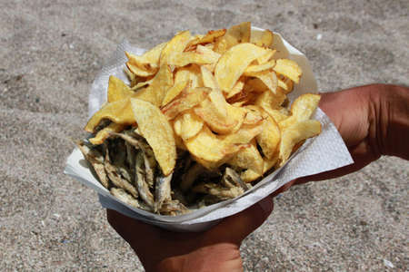 sprat: Closeup chips and fried sprat fish in man s hands