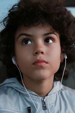 Cute kid is listening music with headset