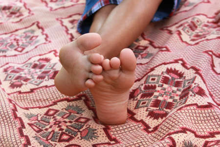 boy feet: Children feet on pink blanket, no face