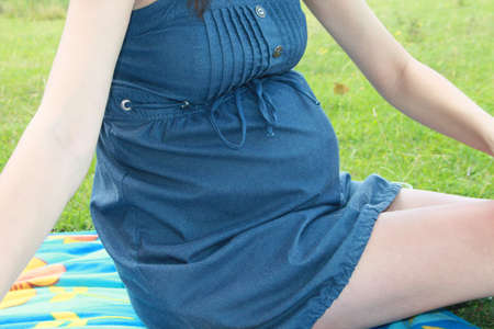 Closeup picture of pregnant woman with blue dress, no face photo