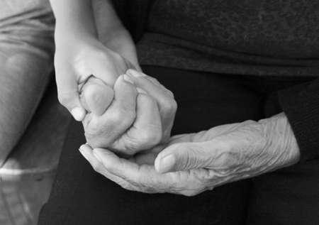 Children hand in grannys hands in black and white photo