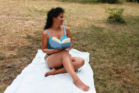Young brunette is reading a book outdoor Stock Photo - 21648754