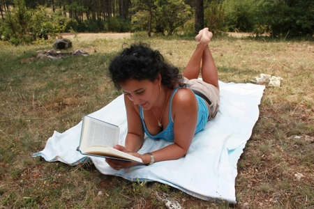 Young brunette is reading a book outdoor Stock Photo - 21648757