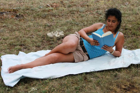 Young brunette is reading a book outdoor photo