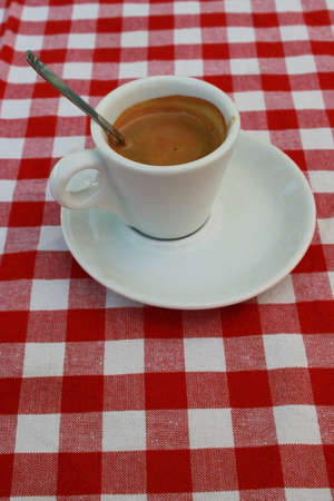 Still life with cup of coffee on checkered tablecloth photo