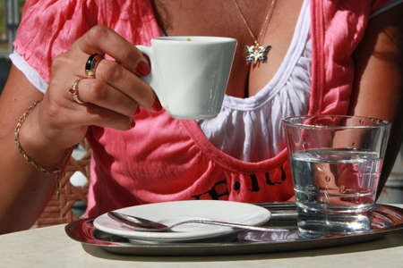 Young woman is drinking a coffee served in silver tray, no face photo