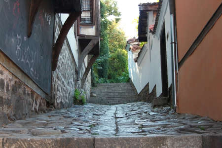 Cobblestone street between red and blue revival houses in Old Plovdiv, Bulgaria photo