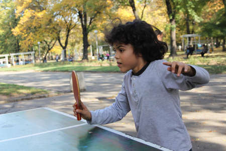 Cute little boy plays ping pong in the park photo