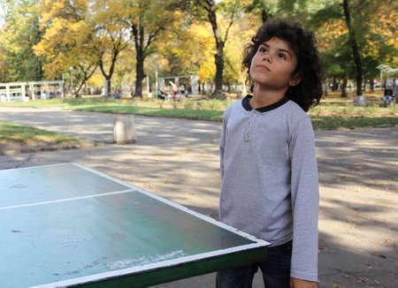 Cute little boy play table tennis in the park photo