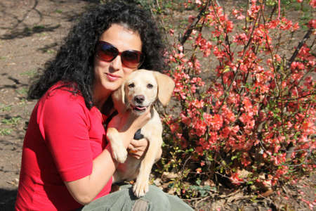 Smiling woman in red blouse with her puppy in the park photo