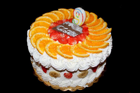 Fruit birthday cake isolated on black photo