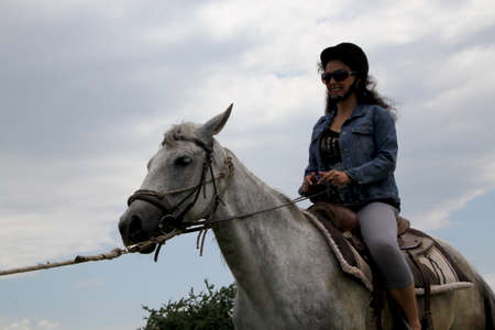 Outdoor picture of a woman on white horse photo