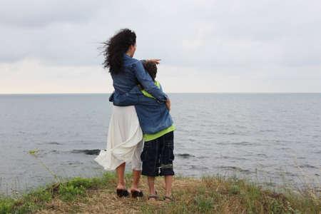 mujer mirando el horizonte: Madre e hijo estancia en la colina mirando al mar
