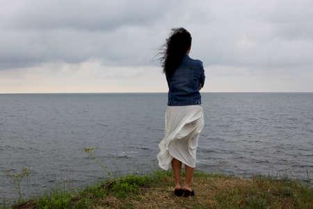 mujer mirando el horizonte: Joven mujer se queda en la colina que mira al mar