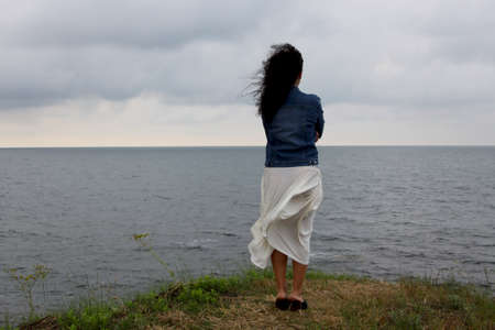 Young woman stays on the hill watching the sea photo