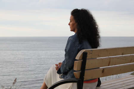 Young woman sits on a wooden bench watching the sea photo