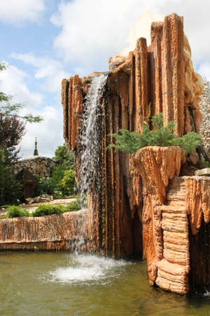 Picturesque decorative waterfall in the city garden  photo