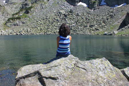 pureness: Curly boy is sitting on the rock in the mountain and he is watching the lake Stock Photo