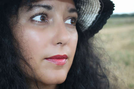 Closeup outdoor portrait of a woman with a hat