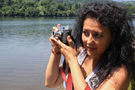 Outdoor picture of a young woman with an old camera photo