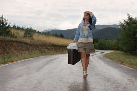 A young woman is caring an old - fashioned suitcase in a rainy day photo