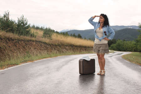 A young woman is standing next to an old - fashioned suitcase in a rainy day photo