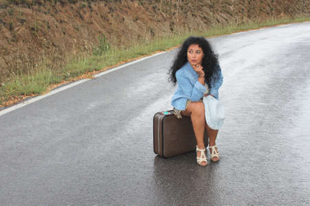 A young woman is sitting on an old - fashioned suitcase in a rainy day photo