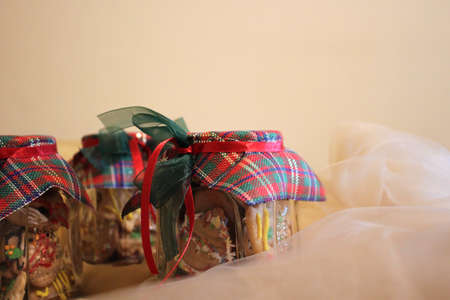 Homemade Christmas cookies in a jar arranged on a beige - pink cloth Banco de Imagens