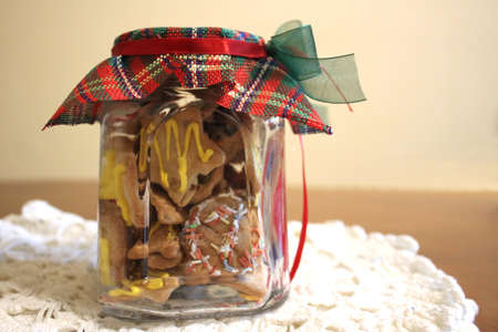 Homemade Christmas cookies in a jar arranged on a beige - pink cloth Stock Photo