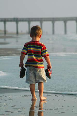 piedi nudi ragazzo: Piccola azienda Barefoot Boy scarpe guardando l'oceano