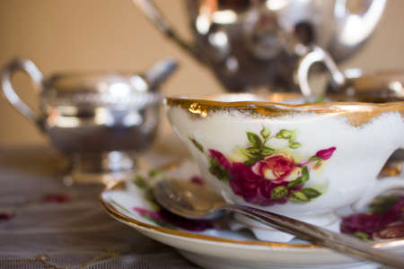 gold table cloth: Antique teacup decorated with red flowers on matching saucer with silver spoon in front of antique sterling silver tea set Stock Photo