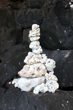 volcanic rock: White coral rocks stacked on top of black volcanic rock on Kauai Hawaii