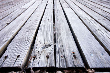 Old faded rotted wooden deck discolored to grey with splintering and dead leaves