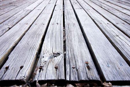 dode bladeren: Oude vervaagde verrotte houten dek verkleurd naar grijs met versplintering en dode bladeren Stockfoto