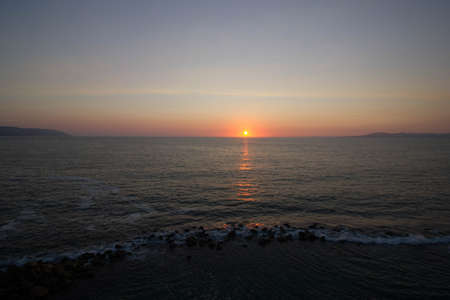 purples: Sun reflects off Pacific Ocean during summer sunset in Puerto Vallarta, Mexico Stock Photo