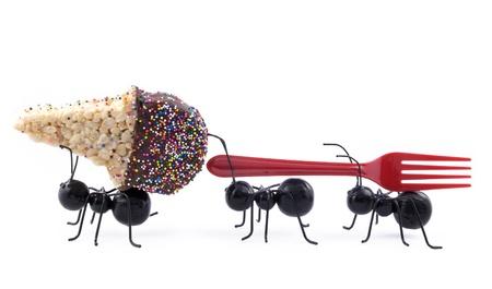 resistencia: Las hormigas de juguete negro llevando un cereal tratan cono de helado y un tenedor, concepto, aislados en fondo blanco, horizontal con espacio de copia Foto de archivo