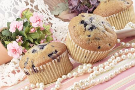 Fresh baked blueberry muffins with a feminine setup with pearls and pink roses, perfect for Mothers Day