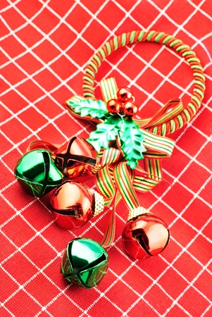 Shiny Christmas jingle bells in red and green with red and white textured cloth background, vivid color photo