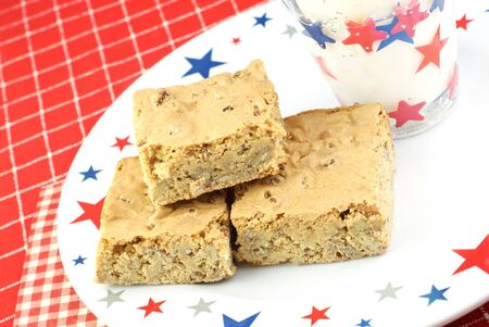 A patriotic plate with Pecan Caramel Chewy Holiday Bars with a glass of milk, copy space photo
