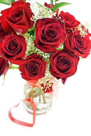 vases: A bouquet of deep red roses in a vase with red heart shape, shallow depth of field with selective focus Stock Photo