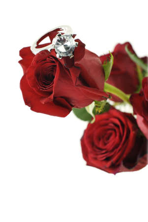 A bouquet of red roses with a sparkling diamond engagement ring on a rose, selective focus on diamond with white background