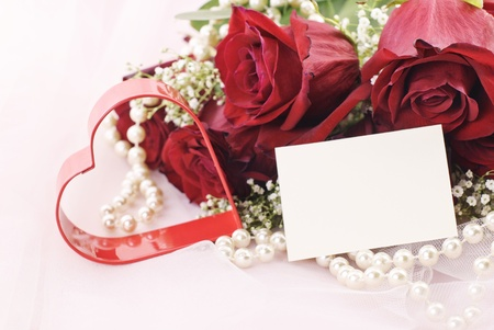 A beautiful bouquet of red roses with red heart, pearls, and gift tag with copy space on pink tulle background photo
