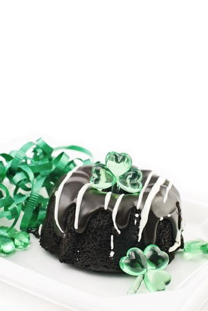 A small Saint Patrick's Day chocolate bundt cake with green ribbons and shamrock decorations, vertical with white copy space Stock Photo - 8925639